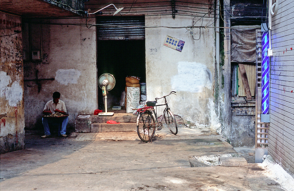 A local man working to sort food which has been left to dry under the suns rays in the backstreets of old Canton (Guangzhou), Guangdong Province, Southern China.