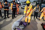 A security guard working on behalf of HS2 forcibly removes an environmental activist from HS2 Rebellion from the road in front of a gate providing access to a site for the HS2 high-speed rail link on 12 September 2020 in Harefield, United Kingdom. Anti-HS2 activists continue to try to prevent or delay works on the controversial £106bn HS2 high-speed rail link in the Colne Valley where thousands of trees have already been felled.