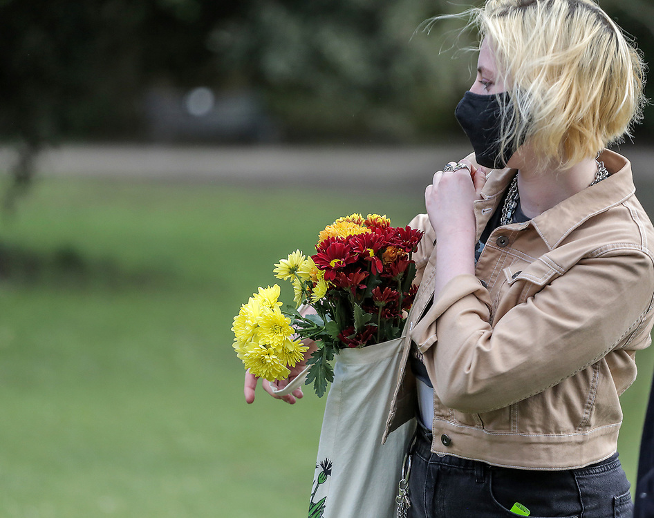 13th, March, 2021. Cheltenham, England. A member of the public holds flowers in memory of Sarah Everard.
