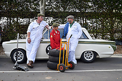© licensed to London News Pictures. 12/09/2015<br /> Goodwood Revival Weekend, Goodwood, West Sussex. UK.<br /> The Goodwood Revival is the world's largest historic motor racing event. Competitors and enthusiasts dress in period fashions recreating the glorious days of the race circuit.<br /> Pictured Mechanics wait with classic Lotus Cortina before a race.<br /> Photo credit : Ian Whittaker/LNP