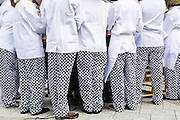 A group of professional chefs wearing traditional black and white checked trousers with white tunic top gather for a briefing at an outdoor event in Belfast, Northern Ireland,  United Kingdom.