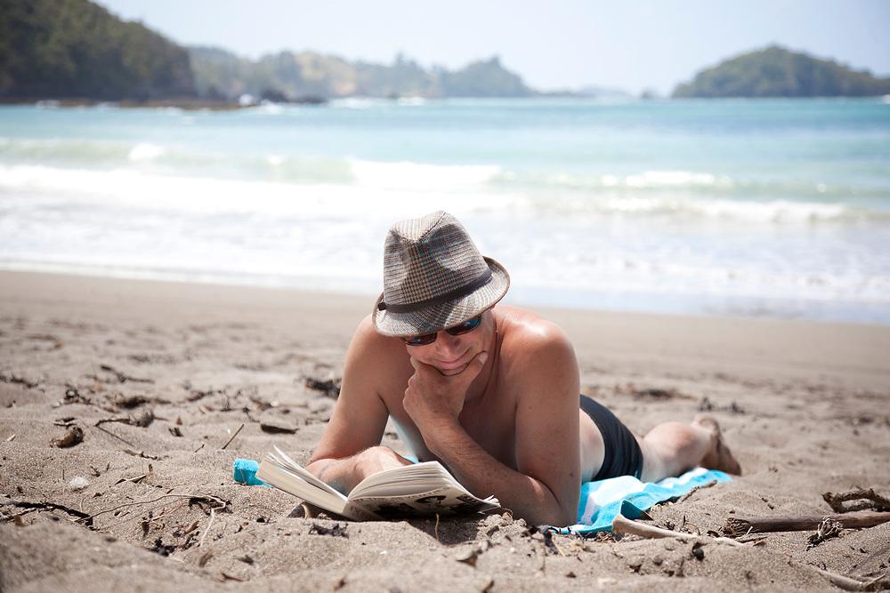 man reading on a beach