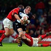Barbarians' Adrian Garvey (c) is tackled by Wales' Robin McBryde (l)