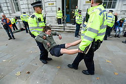 © Licensed to London News Pictures. 09/10/2019. LONDON, UK.  Police remove and detain climate a change activist from outside Cabinet Office in Whitehall during day 3 of Extinction Rebellion's climate change protest in the capital.  Some of the activists had used glued themselves to the road.  Photo credit: Stephen Chung/LNP