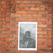 """""""Mira Mexico"""", newspaper exhibition (DETAIL) installed on a wall in Rochester, New York June 30, 2013.<br /> (Credit Image: © Alysia Kaplan)<br /> <br /> Curator<br /> Alysia Kaplan (USA)<br /> <br /> Using photographs taken by Louie Palu relating to the Mexican drug war, this project challenges the reader to take apart this newspaper to see the full photographs and view the content. The goal is to force the reader to dismantle the vehicle used to deliver news and facts and thereby empower the reader to begin to think more critically. There are 16 photos in total, eight that do not relate to violence and eight that focus on violence or the drug business.. Each photograph is printed on a single sheet of newsprint, so if you take the newspaper apart each sheet of paper will have only one photograph on each side. Only eight pictures can be viewed at one time No photo can be entirely seen unless the reader opens and takes the newspaper apart. <br /> <br /> Once the newspaper comes apart it can be put back together in any order the reader wishes. The page spreads can also be hung as an exhibition. With violent images on one side and non-violent images on the other, the reader must become editor, curator or even censor, choosing how many violent photos are seen vs. how many non-violent photographs are seen. This forces the reader to face up to the fact that all delivery of news involves choices, of what to show and tell and what not to show and tell. It also forces the reader to face up to the system of institutions that serves as the gatekeepers in journalism and the visual arts. The questions are obvious. Is the editor censoring? Is the edit a true depiction of the news and the issue? Are violent images being used effectively to tell a story, or to sensationalize the story? The actual newspaper as an object forces the reader to engage in a a multidimensional exercise in journalism, art, and the politics of representation and message manipulation."""