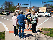 "03 MAY 2020 - PELLA, IOWA: People wait to cross Washington Street, the main street in downtown Pella, Iowa. Pella is a small community in central Iowa. The town's economy is driven by tourism and the Tulip Festival, the largest tourist event of the year, has already by canceled for 2020 because of fears that the festival could become a COVID-19 (Coronavirus/SARS-CoV-2) ""Super Spreader"". The Governor of Iowa reopened 77 of Iowa's 99 counties. The counties that were reopened have reported low incidences of Coronavirus. Marion County, where Pella is located, has reported 12 cases of Coronavirus. There have been 9,169 confirmed cases of Coronavirus in Iowa, including 1,476 cases in the Des Moines area, less than one hour away. Many people from Des Moines drove to Pella this weekend to see the tulips for which the town is famous.     PHOTO BY JACK KURTZ"
