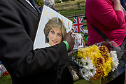 As crowds of royalist well-wishers gather, a spontaneous memorial of flowers, photos and memorabilia grows outside Kensington Palace, the royal residence of Princess Diana who died in a car crash in Paris exactly 20 years ago, on 31st August 2017 in London, United Kingdom. In 1997 a sea of floral tributes also filled this area of the royal park as well as in other relevant areas of London. Then, as now, royalists mourned the People's Princess.