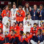 TOKYO, JAPAN August 8:  Five-time Olympic gold medalists Diana Taurasi, (left) and Sue Bird of the United States with the Japanese team during a group photograph with their medals after the United States victory during the Japan V USA basketball final for women at the Saitama Super Arena during the Tokyo 2020 Summer Olympic Games on August 8, 2021 in Tokyo, Japan. (Photo by Tim Clayton/Corbis via Getty Images)