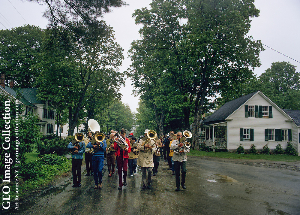 Small band with brass instruments marching down a wet village street in quaint Memorial Day parade around the sparsely populated town of Grafton, Vermont on May 28, 1973. The annual event sponsored is by Grafton Grange association. Baritone horns head up the mostly male musicians.