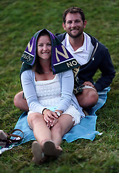 Spectators shelter under an official towel as rain falls on day three of the Wimbledon Championships at the All England Lawn Tennis and Croquet Club, Wimbledon.