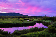Pastel colors paint the sky and reflect in the calm, glass-like waters of the dark water of the Blackwater River in Canaan Valley State Park, West Virginia.