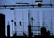 Construction wall of rebar with workers in silhouette