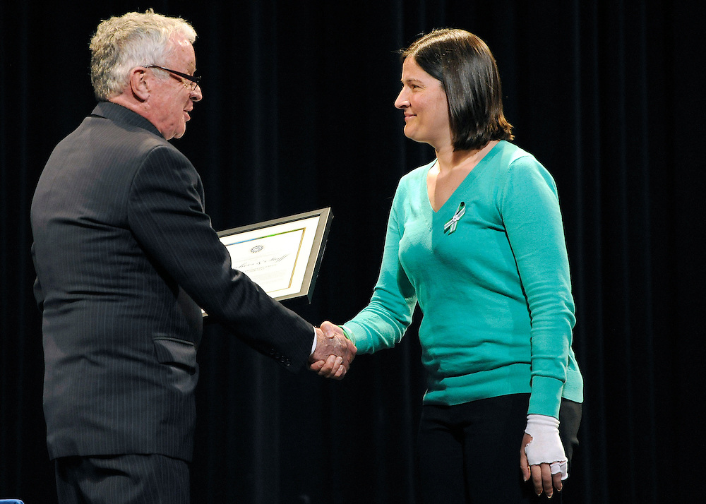 Lead teacher at Sandy Hook Elementary School and survivor of the shooting Natalie Hammond, right, accepts a certificate of commendation from Thomas Kelly, left, in Newtown, Conn., Monday, May 6, 2013. Hammond was shot in the foot, leg, and hand, managing to crawl and hide behind a door. (AP Photo/Jessica Hill)