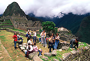 PERU, HIGHLANDS, PREHISPANIC, INCA Machu Picchu; a family visiting the site sitting below houses