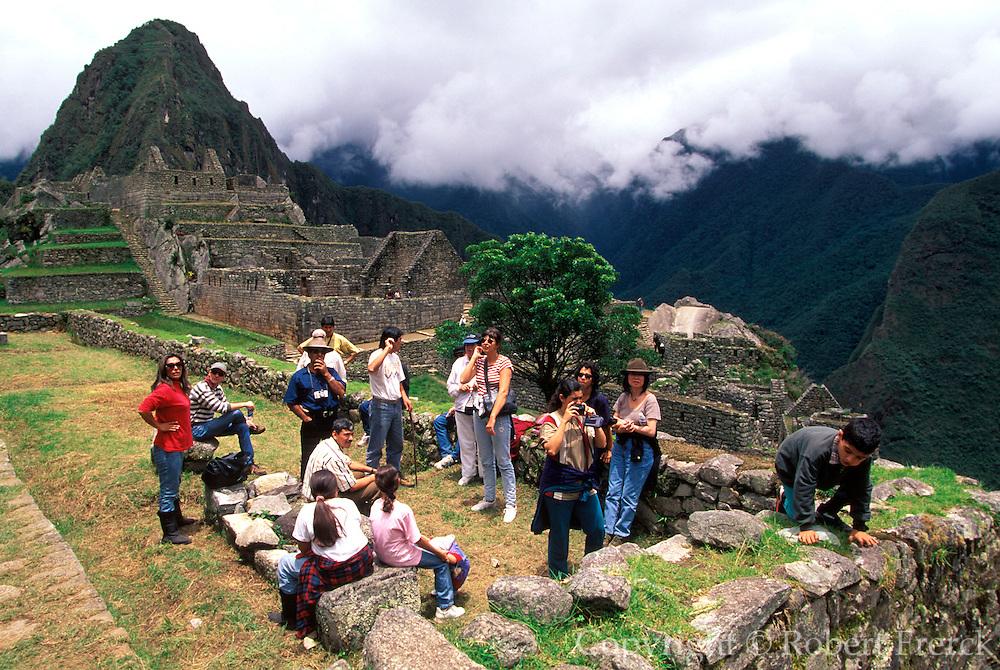 PERU, HIGHLANDS, PREHISPANIC, INCA Machu Picchu; a family visiting the site sitting below houses