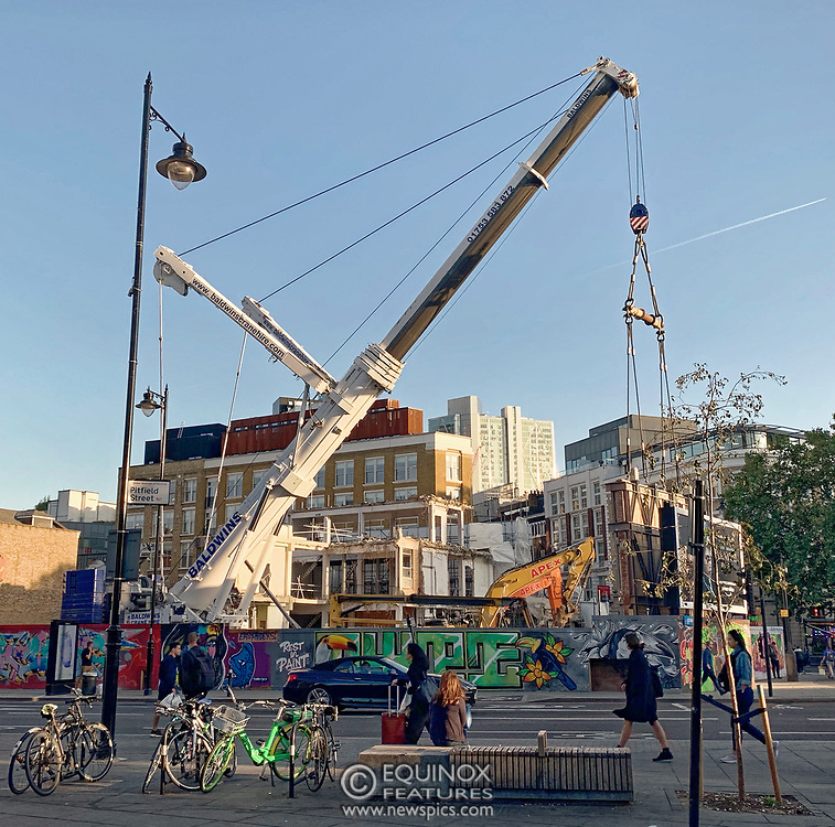 London, United Kingdom - 20 September 2019<br /> EXCLUSIVE SET - Aerial construction specialists and demolition experts use a huge crane to carefully lift intact, a twenty five ton, two-story wall, to preserve a famous Banksy rat image which has been covered up for years. Teams from specialist companies have spent over six weeks cutting around the artwork and fitting custom made eight ton steel supports to enable them to save the historic piece of art. Work has started on the construction of a new twenty seven floor art'otel hotel on the site of the old Foundry building in Shoreditch, east London, and a condition of the planning permission was to preserve the historical Banksy graffiti. A second section of the painting, an image of a TV being thrown through a broken window has already been cut out and moved separately. After the hotel construction is complete the two parts of the Banksy painting will be displayed on the hotel. Our pictures show the stages of work to protect the image, culminating in the lifting of the three story wall by crane. Video footage also available.<br /> Editorial Disclosure: This image is a composite panorama created from a set of images taken within a few seconds of each other.<br /> (photo by: EQUINOXFEATURES.COM)<br /> Picture Data:<br /> Photographer: Equinox Features<br /> Copyright: ©2019 Equinox Licensing Ltd. +443700 780000<br /> Contact: Equinox Features<br /> Date Taken: 20190920<br /> Time Taken: 175915<br /> www.newspics.com