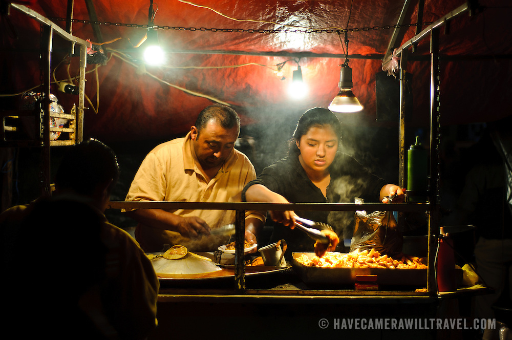 Food vendors serve hot food at night before the famous Sunday market in Chichicastengo. Chichicastenango is an indigenous Maya town in the Guatemalan highlands about 90 miles northwest of Guatemala City and at an elevation of nearly 6,500 feet. It is most famous for its markets on Sundays and Thursdays.