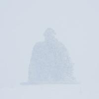 The monument of Bárður Snæfellsás in winter snowstorm. Arnarstapi, Snæfellsnes Penisula, West Iceland.