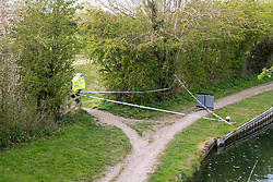 © Licensed to London News Pictures. 27/04/2021. Aylesbury, UK. A police cordon on a path following a fatal assault near Bridge 14 on the Grand Union Canal near Broughton in Aylesbury at about 12.20pm on Monday 26/04)/2021. Police officers found a man with serious injuries and despite the efforts of emergency services the man died at the scene. Photo credit: Peter Manning/LNP