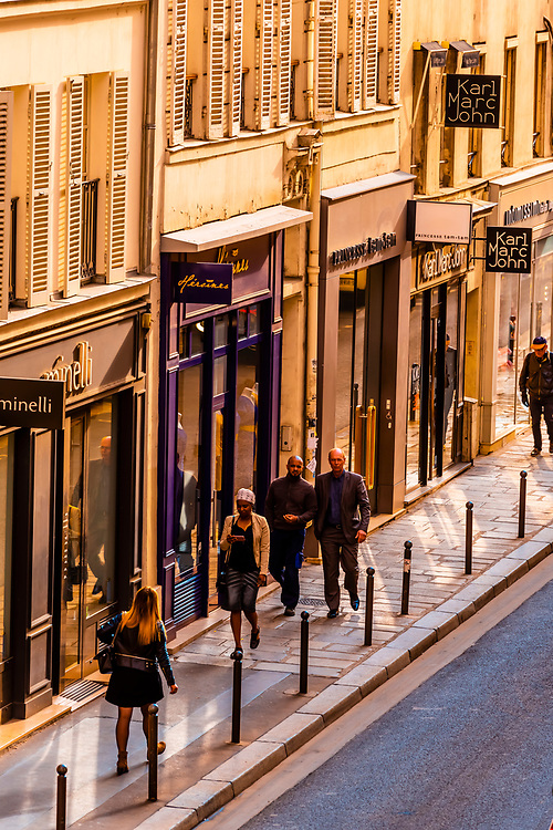 High angle view of pedestrians walking on the sidewalk along Rue St. Dominique, Paris, France.