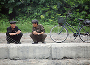 North Korean men talk in the the town of Sunuiju  on the Sino-Dprk border July 9, 2006. North Korea promised to use force against any country that tries to pressure it into a halt of its missile launches. DPRK, north korea, china, dandong, border, liaoning, democratic, people's, rebiblic, of, korea, nuclear, test, rice, japan, arms, race, weapons, stalinist, communist, kin jong il