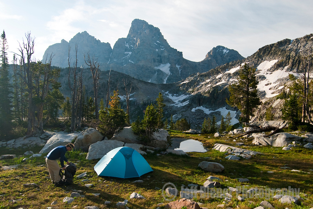 A young man searches his backpack while at camp in Grand Teton National Park, Wyoming.