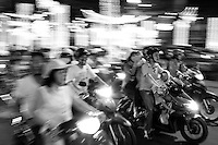 Families whizz by on motorbikes on the packed streets of Saigon.