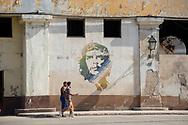 "Two men in the old town of Havana walk past a mural of Ernesto ""Che"" Guevara. (Habana Vieja, Cuba - December 16, 2014)"
