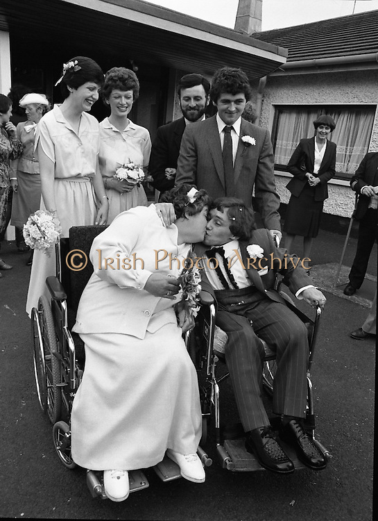Historic Wedding Bells For Disabled Couple,  (N81)..1981..20.06.1981..06.20.1981..20th June 1981..Happy wedding bells chimed today for the first disabled couple in residential care to marry in the Republic of Ireland. The happy couple are Marie Skully and Pat Linehan and they were married in a special ceremony in The Cara Cheshire Home in the Phoenix Park. Both Marie and Pat are confined to wheelchairs because of their disabilities. After honeymoon, they will make their home in specially adapted quarters within the Cheshire residence..A kiss for the blushing bride, Pat is pictured kissing Marie after the wedding ceremony.`Happy bridesmaids and groomsmen complete the picture..If you know the names of the priest and family members why not let us know and we will add them to the caption.