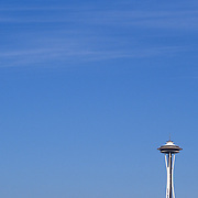 Space Needle in Seattle, Washington. The landmark is shown in small scale aginst a blue sky.