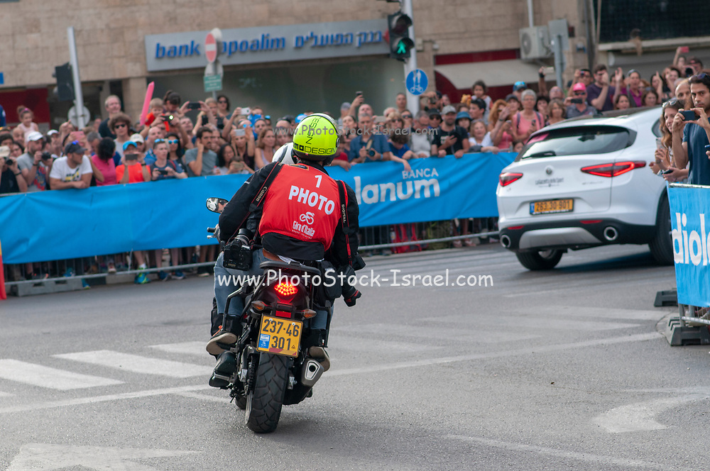 Press photographer chasing the action on a motorcycle