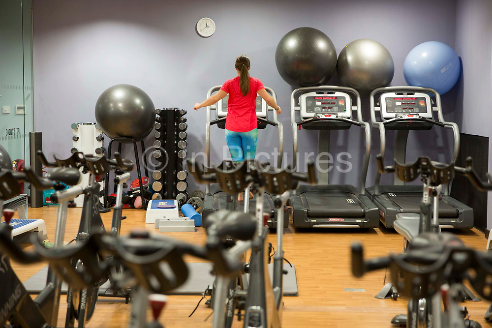 A women running on a treadmill machine surrounded by swiss balls, hand weights and other exercise equipment in a gym in London, England, United Kingdom.