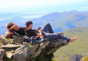 Two male walkers resting on rock overhang, Mount Snowdon, Gwynedd, Snowdonia, north Wales, UK
