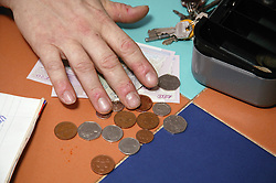 Close up of hand counting money from a cash box,