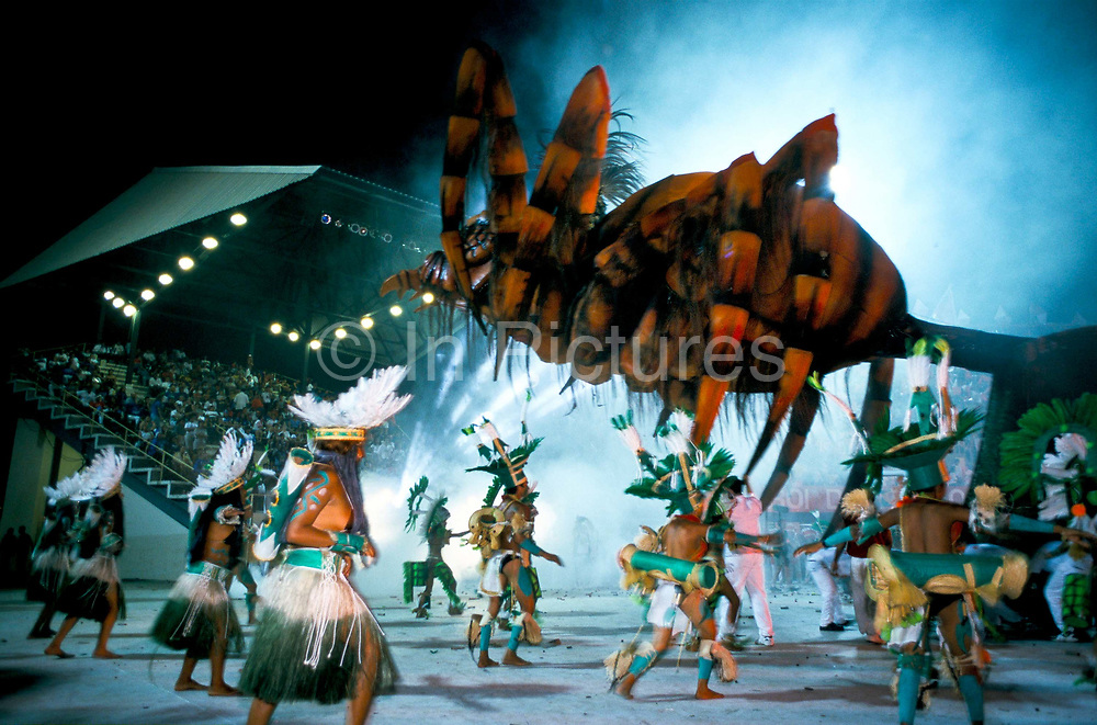 """Brazil -Parintins - The Boi Bumba carnival and a group of participants dance to the """"Tucandeira"""", an indian ritual with giant insects and give  an infectious rhythm    to the celebrations during the three day event deep in the Amazon. The carnival serves to celebrate and re-enact Indian traditions and perpetuate myths and legends. It has evolved over time and involves the battle between to opposing bulls, known as Garantido and Caprichoso"""