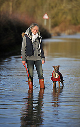 © Licensed to London News Pictures. 27 January 2013. Ascott Under Wychwood, Oxfordshire. Amelia and her dog Molly walk down the flooded road. Floods after the snow melted. Photo credit : MarkHemsworth/LNP