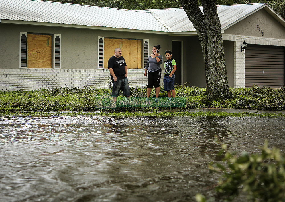 September 11, 2017 - Kissimmee, Florida, USA - Kissimmee, Fla. residents Robert Gonzalez, his wife Maria and son David, 10, survey the flooded Town & Country Drive in front of their home, which is located on Sweetbriar Court where it meets Town & Country, on Monday, Sept. 11, 2017. They said they had a little water get into their garage, but it quickly receded and there was no damage. (Credit Image: © Jacob Langston/TNS via ZUMA Wire)
