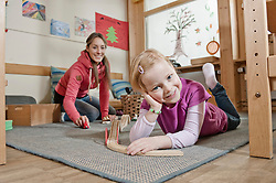 Little girl playing with wooden railroad in her kindergarten