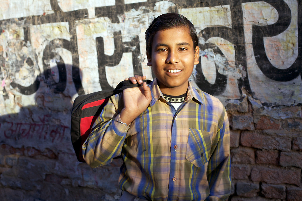 A 13 years old boy from Bikaner, India is posing for a portrait on the way to school.