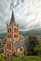 View of St Peter Church, and includes birds, mountains and cloudy skies in the background, Bacharach, Germany.
