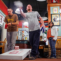 102314       Cable Hoover<br /> <br /> Cameron Thomas, center, and others compete in the weekly cornhole tournament at Sammy C's Sports Pub in Gallup Thursday. The current league will conclude in early December but pub owner Sammy Chioda said he expects to host additional leagues through the winter.