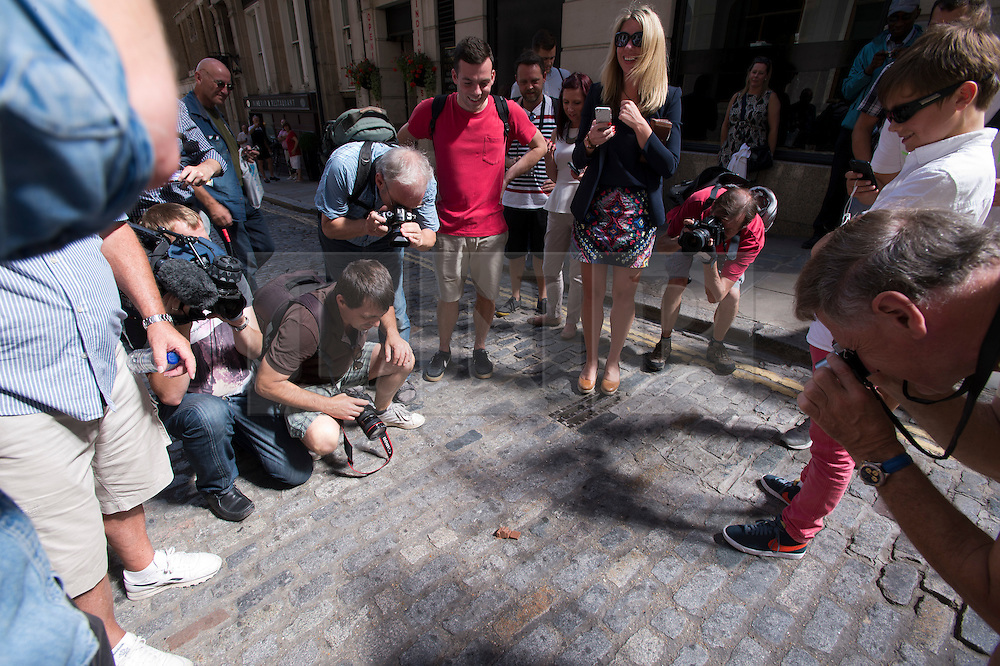 © London News Pictures. 04/09/2013. London, UK. Members of the public watch a piece of chocolate melt on the road caused by light reflected off 20 Finchurch Street in the financial district of central London. The building, which has been named unofficially the 'Walkie Talkie' building because of its shape, intensifies the suns light and reflects it onto the street below. There have been reports of damage to vehicles and local shops caused by the heat of the reflected light. Photo credit: Ben Cawthra/LNP