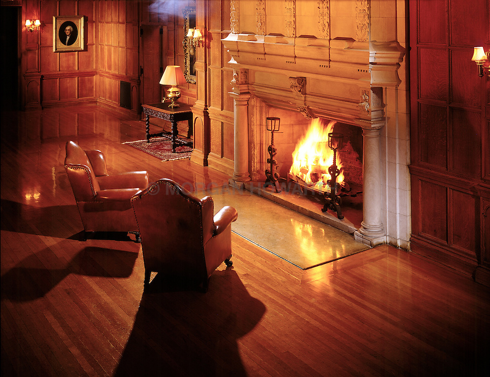 Mansion wood paneled ballroom with two leather chairs in front of big stone fireplace