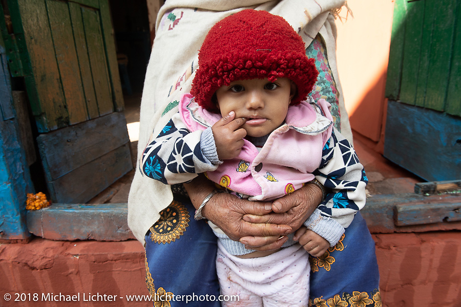 Nepalese grandma with her granddaughter on the main street of Tatopani on Day-7 of our Himalayan Heroes adventure riding from Tatopani to Pokhara, Nepal. Monday, November 12, 2018. Photography ©2018 Michael Lichter.