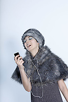 studio shot portrait of a beautiful woman russian type in a fur coat and hat using her multimedia player as a microphone and singing
