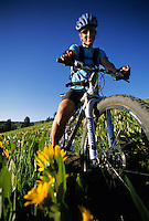 A portrait of a smiling young woman sitting on a mountain bike in Jackson Hole, Wyoming.