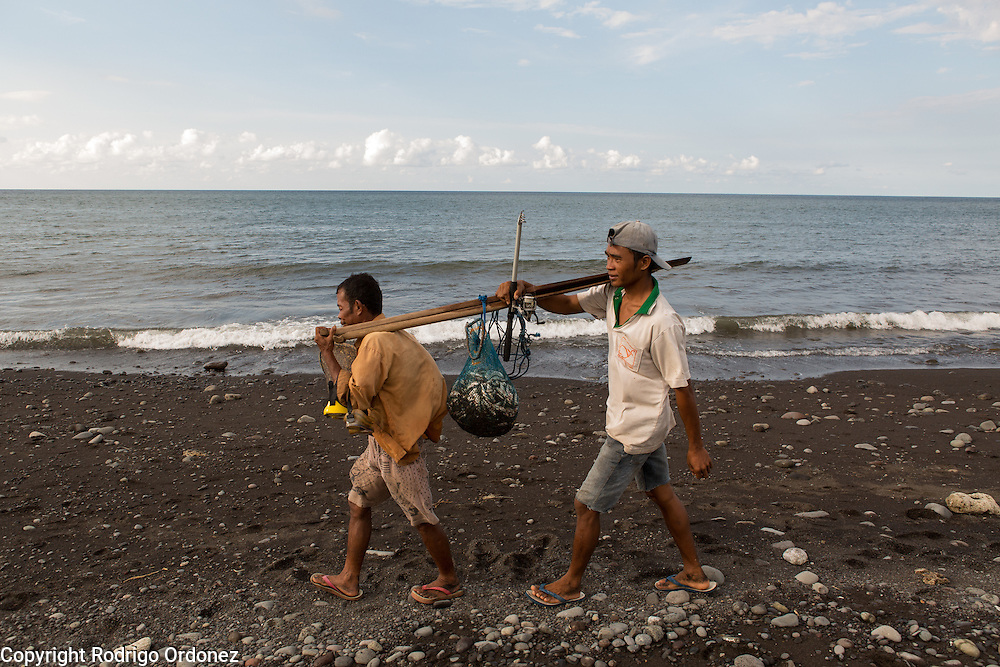 (From left to right) Fishermen Hirman, 40, and Kursia, 26, carry their catch home to produce processed fish in Lepek Loang, Belanting, Sambelia district, East Lombok, West Nusa Tenggara province, Indonesia.