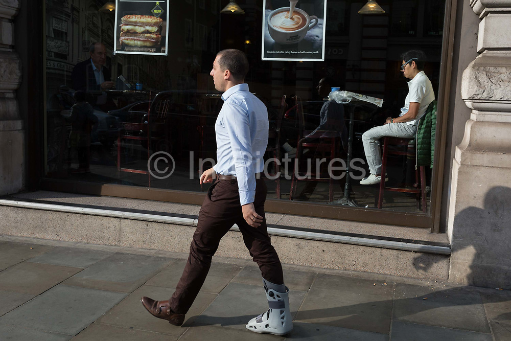 A man sits in the sunlit window of a central London cafe, on 25th October 2018, in Piccadilly, London, England.