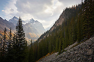 A dramatic sunset casts evening light through a valley in Rocky Mountain slope in Banff National Park, Alberta, Canada.