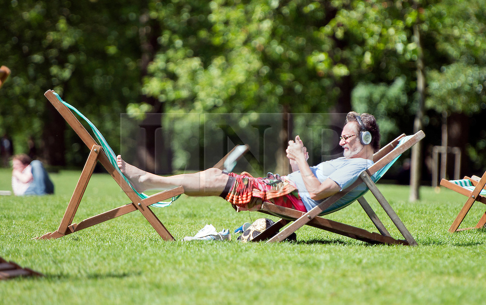 © Licensed to London News Pictures. 10/06/2014. London, UK. A man relaxes in Green Park.  Londoners enjoy the sunny weather today 10th June 2014. Photo credit : Stephen Simpson/LNP